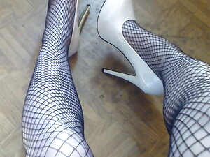 Klaudia dressed in fishnet stockings and white high heels